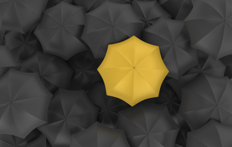 yellow umbrella in a sea of black umbrellas
