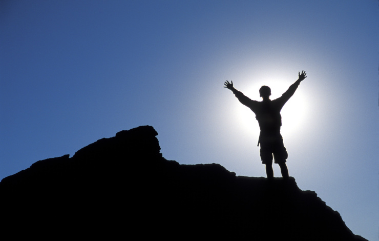 man standing on top of a mountain celebrating success