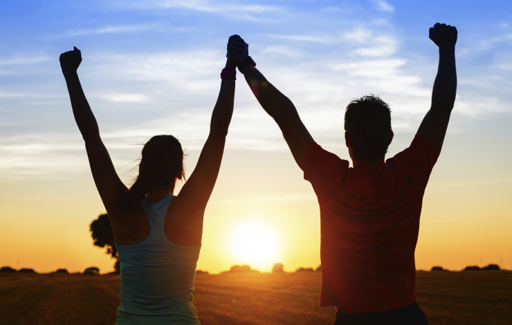 two people celebrating success at sunrise