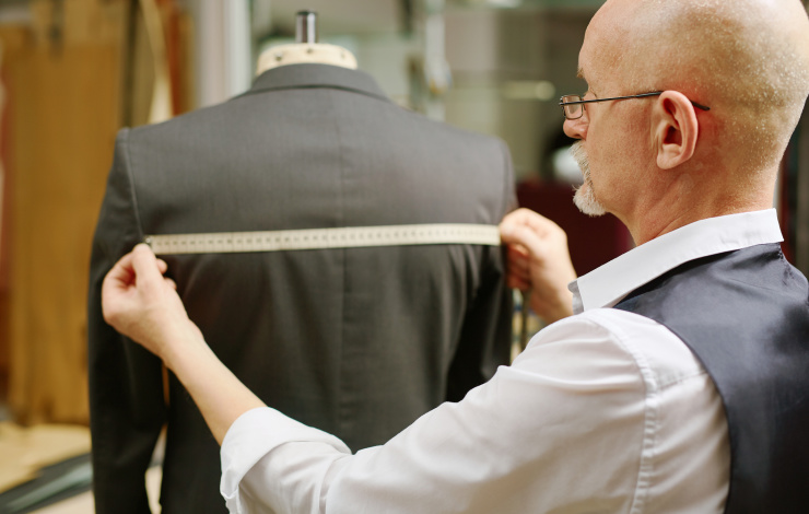 A tailor measuring the back of a suit jacket