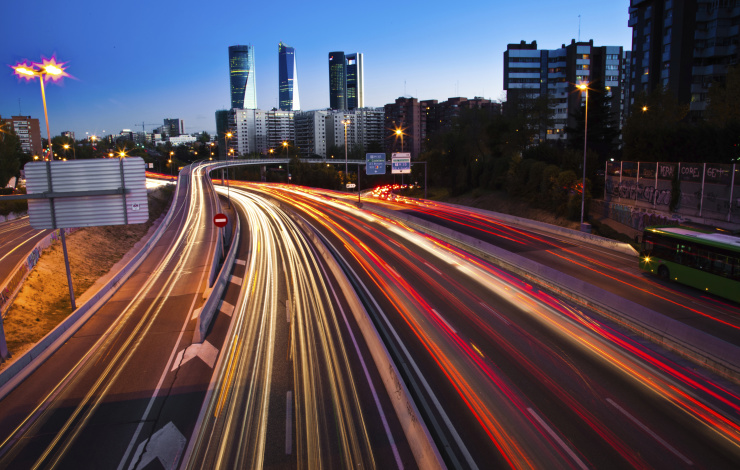 image of a cityscape with highway traffic blurred