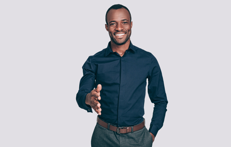 Handsome young African man stretching out hand for shaking and smiling to you while standing against grey background