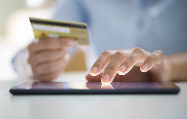 woman shopping online with credit card out and ready to buy