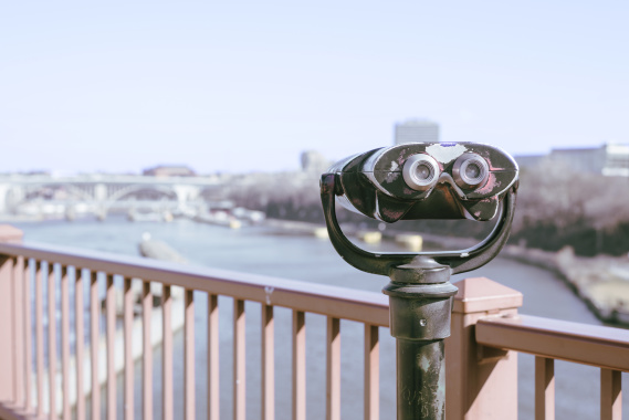 retro binoculars on bridge overlooking city