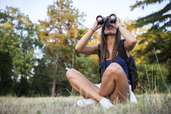 Young woman using binoculars in nature