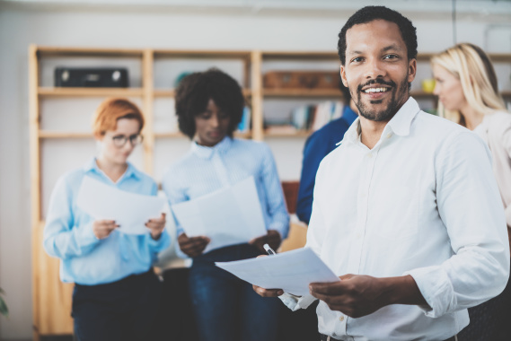 African american entrepreneur in white shirt holding papers in hands and smiling at the camera.Teamwork concept in modern office. Horizontal,blurred background