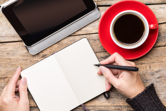 woman writing in notebook with tablet and coffee