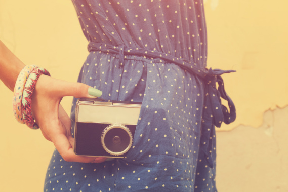 hipster girl holding an old camera with instagram filter