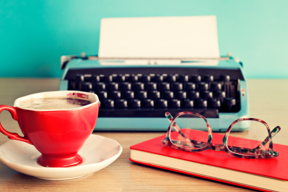 Typewriter on desk with coffee and glasses
