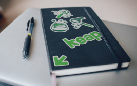 Picture of a notebook and pen on top of a laptop. There are Keap branded stickers on the notebook.