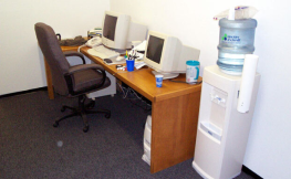 Picture of desk and computers in first real office space.