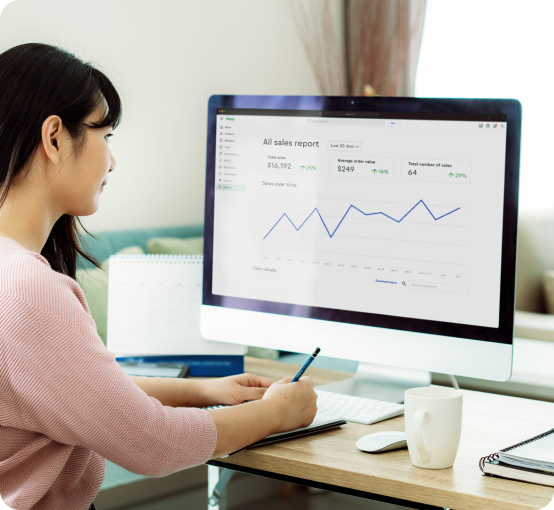Woman using Keap to generate sales reports.