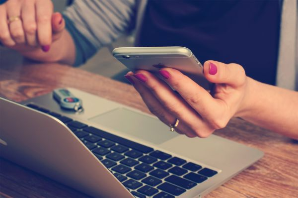 woman looking at mobile phone and working on laptop