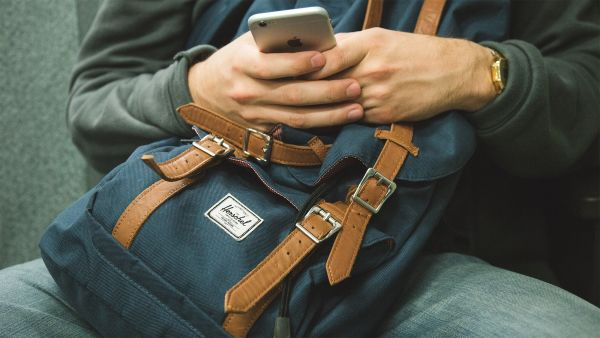 man holding backpack and texting on iPhone