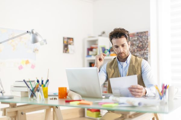 Man working on laptop while holding a document in his hand