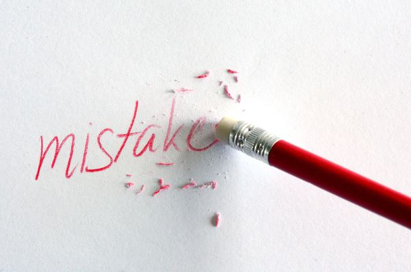 Red pencil erasing the word mistake