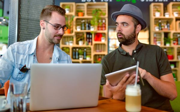 Two guys at a coffee shop looking at a tablet