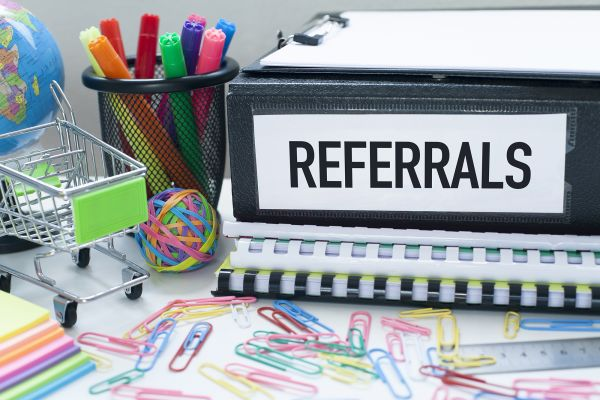 Office supplies and binder with client referral