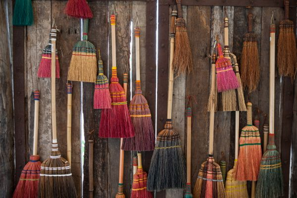 A wall of hanging brooms