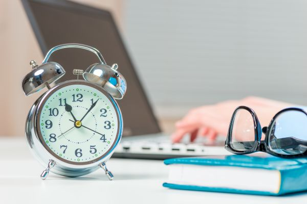 Person working on laptop with a focus on the desk clock