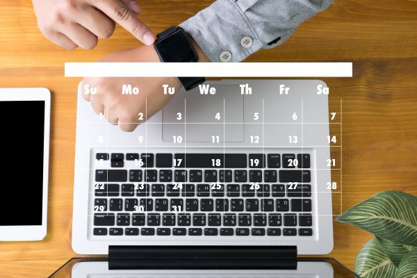 Laptop with an image of a calendar over the keyboard and a person's arm with a watch