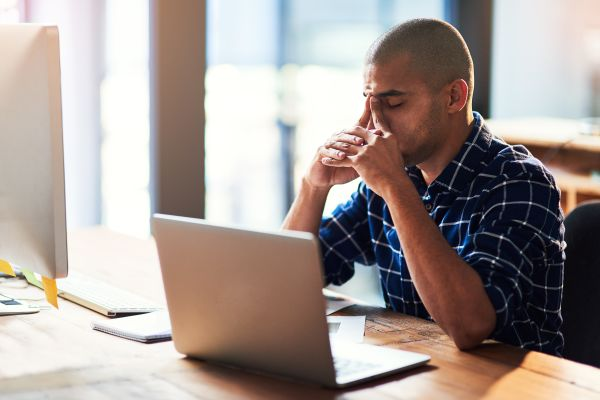 Man feeling stressed working in front of laptop